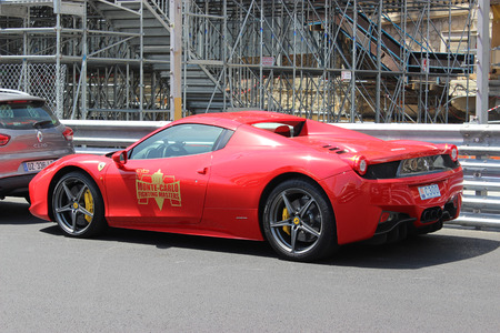 montecarlo: Monte-Carlo, Monaco - April 28, 2016: Red Ferrari 458 Italia Parked on the Street in Monaco. Guardrail of the Monaco Grand Prix in the Background