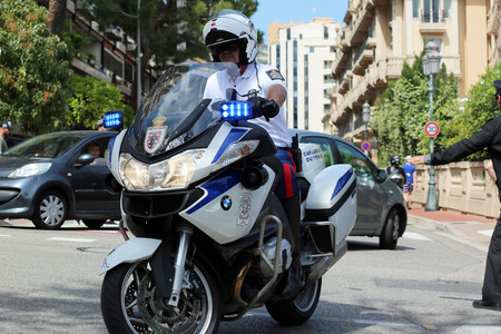 a white police motorcycle: Monte-Carlo, Monaco - May 28, 2016: Police Motorcyclist Escort of the Prince of Monaco during the Monaco Formula 1 Grand Prix 2016 Editorial