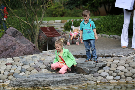 waters  edge: Monte Carlo, Monaco - May 18, 2016: Young Children Playing at the Waters Edge in the Japanese Garden of Monaco in the South of France
