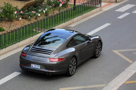 carrera: Monte-Carlo, Monaco - May 18, 2016: Luxury Black Porsche 911 Carrera S on Avenue Princesse Grace in Monte-Carlo, Monaco in the south of France Editorial