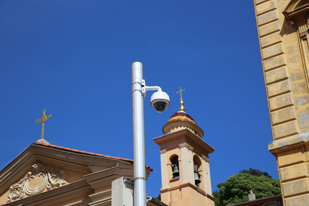 cctv camera: Dome Type Outdoor CCTV Camera on Street Lamp in Nice, Architecture of a Church in the Background Stock Photo