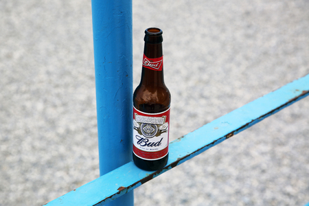 budweiser: Menton, France - May 14, 2016: Bottle of Budweiser Beer on a Blue Metal Fence, Beach in the Background