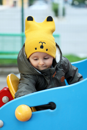 Cute Baby Boy With A Funny Yellow Hat And A Winter Jacket At The Outdoor Playground. Close Up Portrait View Фото со стока