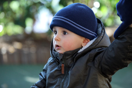Close Up Portrait Of Cute Baby Boy Wearing A Blue Knit Winter Hat And Green Winter Parka
