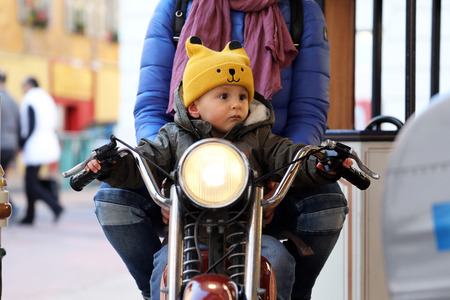 Cute Baby Boy Sitting On A Vintage Motorcycle With His Mom, The Little Boy On The Carousel, Close Up Portrait