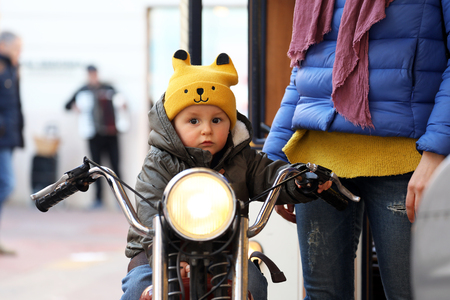 Cute Baby Boy Sitting On A Vintage Motorcycle, The Little Boy On The Carousel, Close Up Portrait