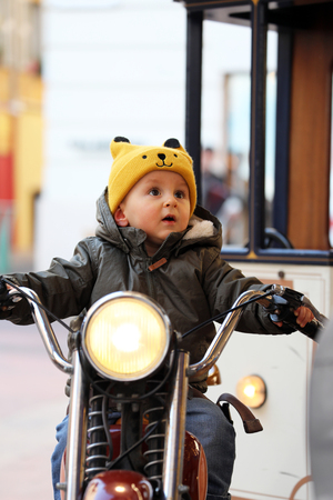 Cute Baby Boy Sitting On A Vintage Motorcycle, The Little Boy Is Laughing On The Carousel, Close Up Portrait 스톡 콘텐츠