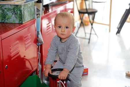 Cute Baby Boy Playing With Firefighter Ride-On Toy Car At Home, Close Up Portrait