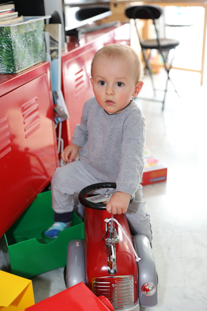 Cute Baby Boy Posing With Firefighter Ride-On Toy Car At Home, Close Up Portrait