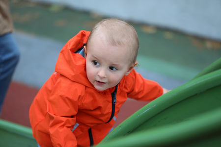Beautiful Baby Boy With Orange Raincoat Climbing Up The Slide, Close Up Portrait View 스톡 콘텐츠