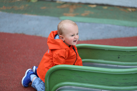 Baby Boy With Orange Raincoat Climbing Up On Slide, Close Up Portrait View