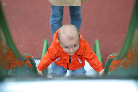 Baby Boy With Orange Raincoat Climbing Up The Slide, Close Up Portrait View