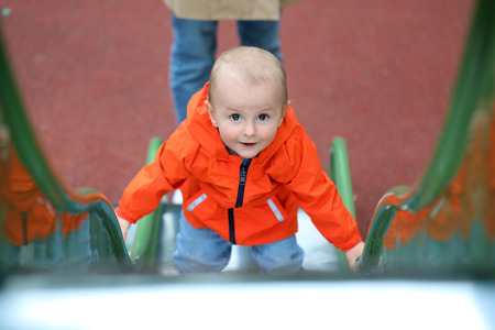 Smiling Cute Baby Boy With Orange Raincoat Climbing Up The Slide, Close Up Portrait View