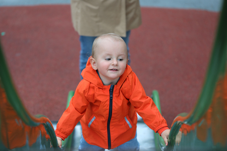 Smiling Cute Baby Boy With Orange Raincoat Climbing Up The Slide