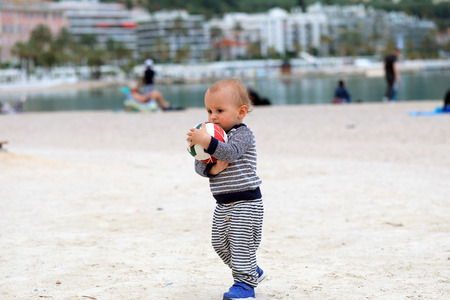 Cute Blond Baby Boy is Holding a Soccer Ball on Sand on Sea Beach in Menton, France on the French Riviera