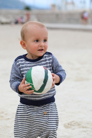 Adorable Blond Baby Boy is Holding a Soccer Ball on Sand on Sea Beach