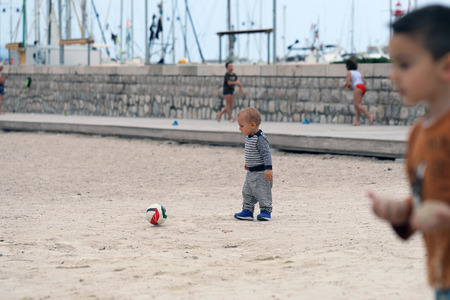 Baby Boy is Playing With a Soccer Ball on Sand on Sea Beach 스톡 콘텐츠