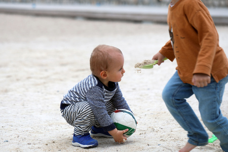 Adorable Blond Baby Boy is Playing With a Soccer Ball on Sand on Sea Beach 스톡 콘텐츠