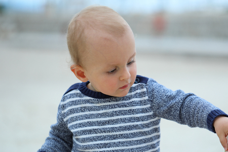 Beautiful Blond Baby Boy Wearing A Blue And White Sweater On The Sandy Beach, Close Up Portrait 스톡 콘텐츠