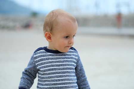 Cute Blond Baby Boy Wearing A Sweater On The Sandy Beach, Close Up Portrait