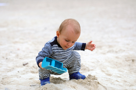 Cute Baby Boy Playing With Sand And Blue Plastic Shovel On The Sea Beach