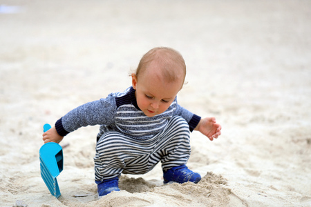 Adorable Baby Boy Playing With Sand And Blue Plastic Shovel On The Beach 스톡 콘텐츠