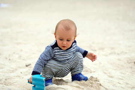 Cute Baby Boy Playing With Sand And Blue Plastic Shovel On The Beach