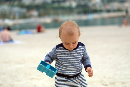 Adorable Baby Boy Playing With Sand And Blue Plastic Shovel On The Sea Beach