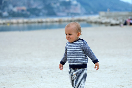 Beautiful Blond Baby Boy Wearing A Blue And White Sweater, Walking On The Sandy Beach, Close Up Portrait 스톡 콘텐츠