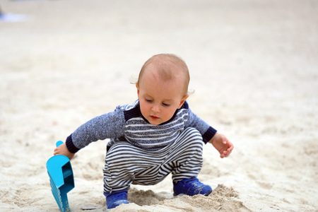 Cute Baby Boy Is Playing With Sand And Plastic Shovel On The Beach