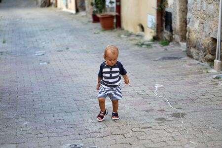 Cute Baby Boy Walking Alone In The Street In The Old Town Of Castellar On The French Riviera, France, Europe