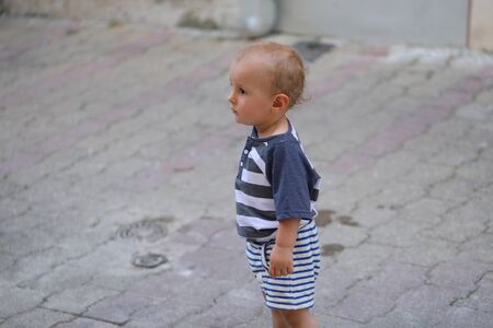 Baby Boy Walking Alone In The Street In The Old Town Of Castellar On The French Riviera, France, Europe