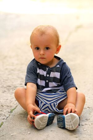 Cute Baby Boy Sitting On The Floor In The Street, Close Up Portrait