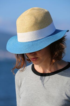 Mysterious Beautiful Woman In Straw Hat At The Beach. Close Up Portrait