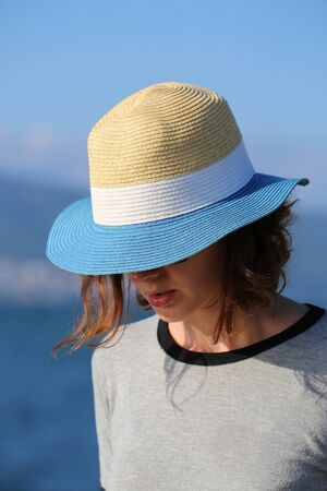 Mysterious Young Woman In Straw Hat At The Beach. Close Up Portrait