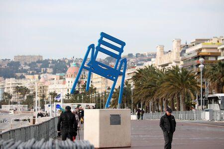 Nice, France - February 6, 2020: The Blue Chair Sculpture, Symbol Of Nice, People Walking On Promenade Des Anglais In Nice City On The French Riviera, France, Europe