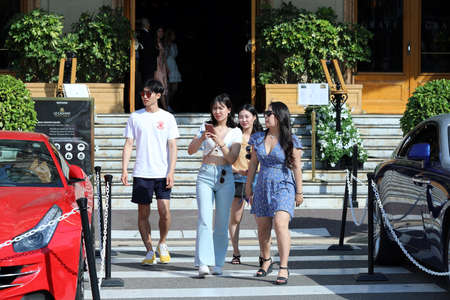 Monte-Carlo, Monaco - June 20, 2019: Group Of Young Asian Tourists In Front Of The Monte-Carlo Casino In Monaco, Asian People Photographing Luxury Cars Editorial