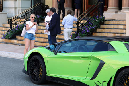 Monte-Carlo, Monaco - June 20, 2019: Woman Photographing A Green Lamborghini Aventador LP 750-4 SV Coupe With Her Smartphone, Supercar Parked In Front Of The Hotel De Paris Monte-Carlo In Monaco On The French Riviera Editorial
