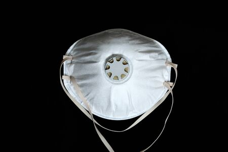 White Surgical Mask FFP2 To Protect Against Virus Infection Coronavirus COVID-19, Isolated On Black Background, Close Up View Foto de archivo