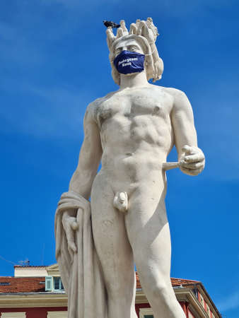 Nice, France - June 9, 2020: Close Up Of Apollo With Surgical Mask During Covid-19 Time, Fountain Of The Sun With A Marble Statue Of On Place Massena In Nice, French Riviera, France, Europe