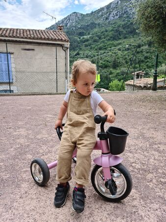 Cute Little Boy Riding A Tricycle On The Square, Typical French Village Square In Gorbio, Europe