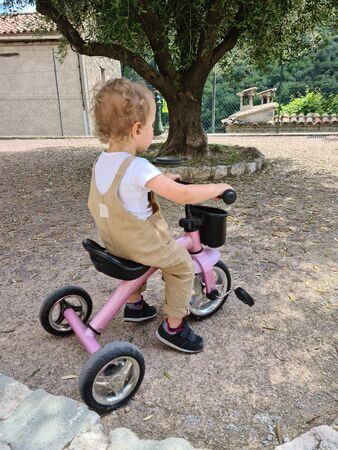 Little Boy Riding A Tricycle On The Square, Typical French Village Square In Gorbio, Europe Foto de archivo