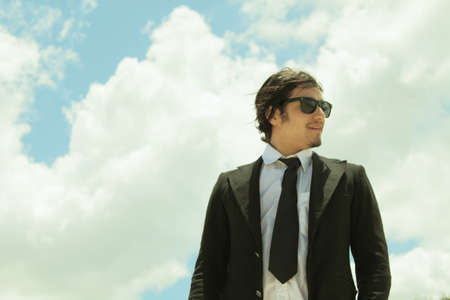 Young Office Man With sunglasses and sky background photo