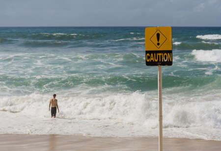 Caution sign due to dangerous surf with man entering water