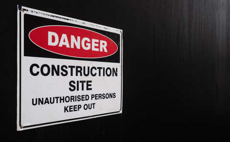 Construction site warning sign, against a black painted fence