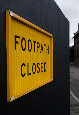 Yellow, footpath closed safety sign on a black fence outside a construction site