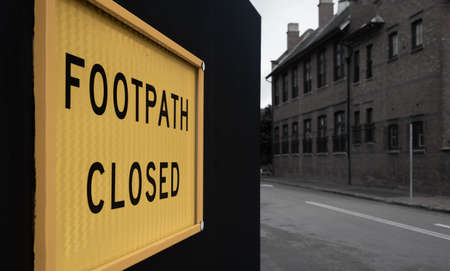 Yellow, footpath closed safety sign on a black fence outside a construction site Stock Photo - 119953355