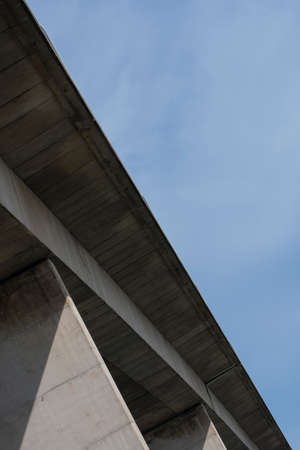 Details of concrete bridge over a river, against a clear blue sky