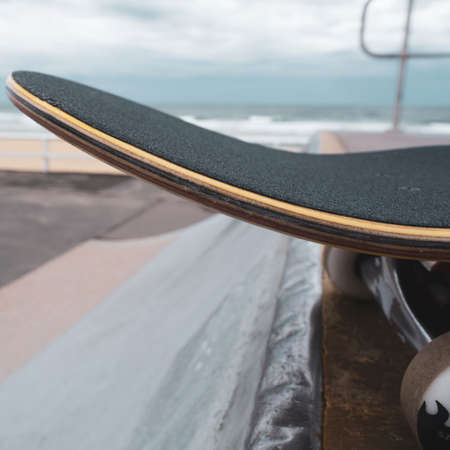 Close up of skateboard on top of a ramp at a beachside skate park. Imagens