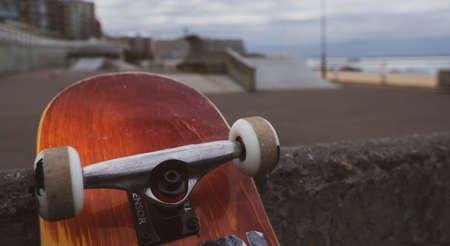 Close up of skateboard leaning against an obstacle at a beachside skate park.